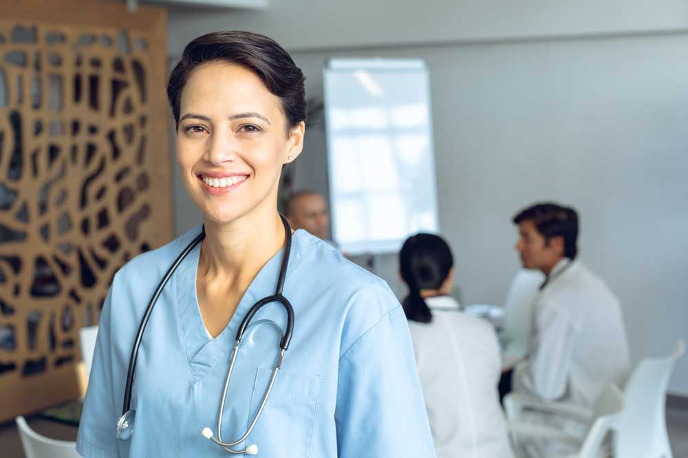 Female nurse in blue scrubs smiling and greeting new patients