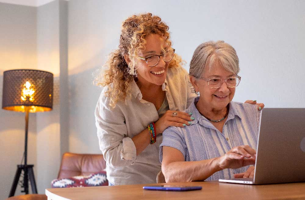 blonde-lady-teaching-an-older-woman to use-a-computer