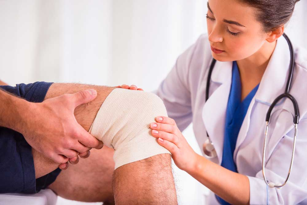 Man with knee injury being seen by ER doctor