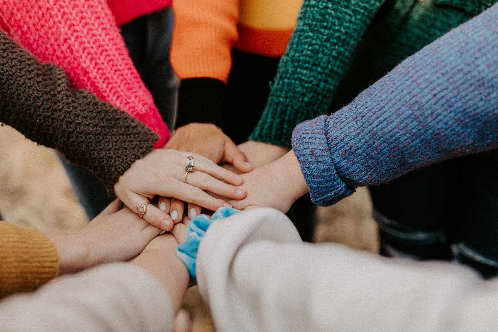 A group of people piling hands in a huddle